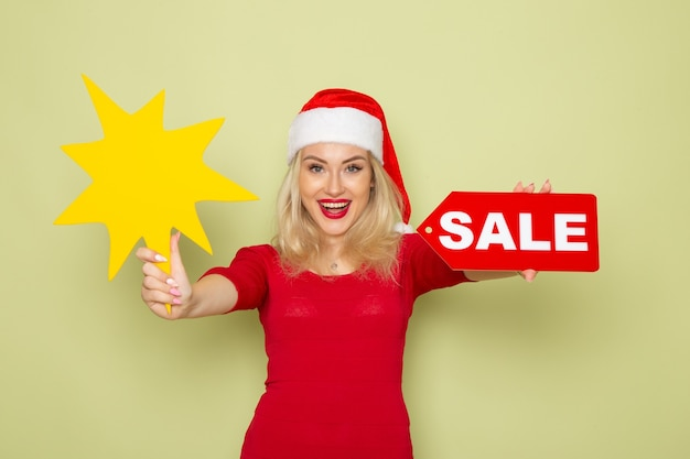 Вид спереди симпатичная женщина, держащая распродажу, и большая желтая фигура на зеленой стене, снег, эмоция, праздник, рождество, новый год, цвет
