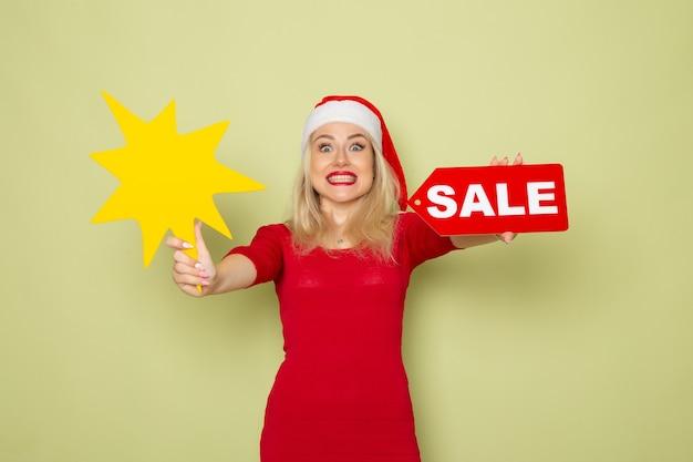 Вид спереди симпатичная женщина, держащая распродажу, и большая желтая фигура на зеленой стене, снежная эмоция, праздник новогоднего цвета