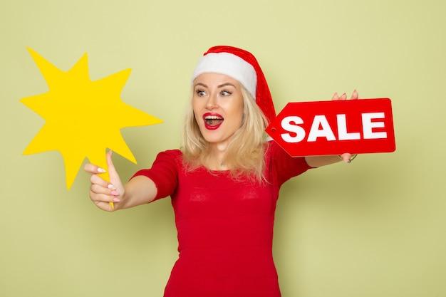 Вид спереди симпатичная женщина, держащая распродажу, и большая желтая фигура на зеленой стене, снег, эмоции, праздники, рождество, новый год, цвет
