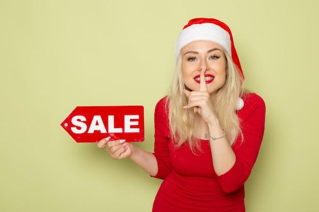 Вид спереди симпатичная женщина, держащая распродажу, пишет на зеленой стене, эмоция, праздник, рождество, новый год, цвет