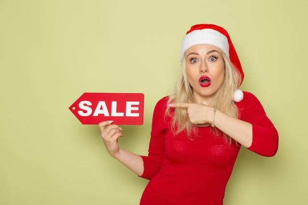 Вид спереди симпатичная женщина, держащая распродажу, пишет на зеленой стене, снежная эмоция, цвет рождества, нового года