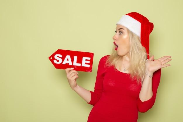 Вид спереди симпатичная женщина, держащая распродажу, пишет на зеленой стене, снег, эмоция, праздник, рождество, новый год, цвет