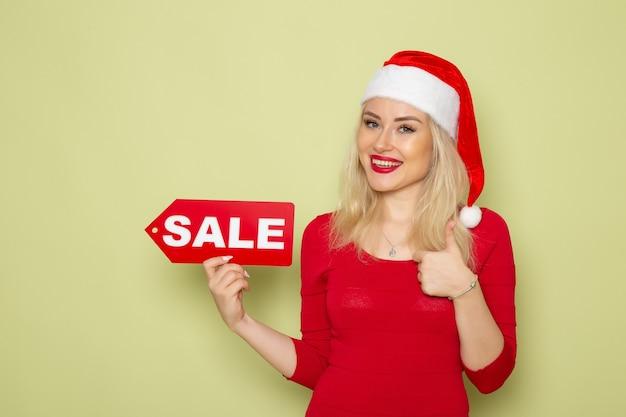 Вид спереди симпатичная женщина, держащая распродажу, пишет на зеленой стене, снег, эмоции, праздники, рождество, новый год, цвет