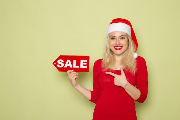 Вид спереди симпатичная женщина, держащая распродажу, пишет на зеленой стене, снег, эмоции, праздники, рождественские новогодние цвета
