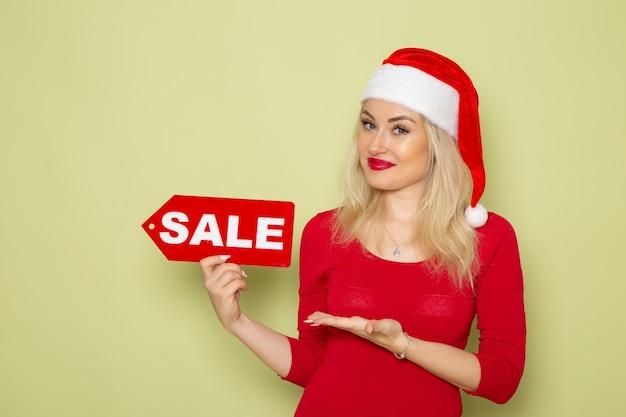 Вид спереди симпатичная женщина, держащая распродажу, пишет на зеленой стене, снег, эмоции, праздники, рождество, новый год