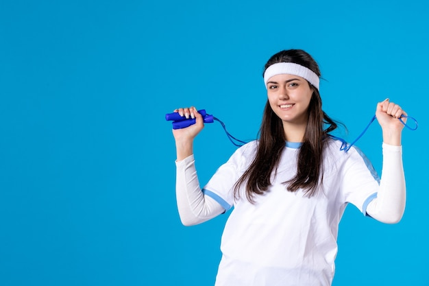 Front view pretty female holding skipping rope on blue