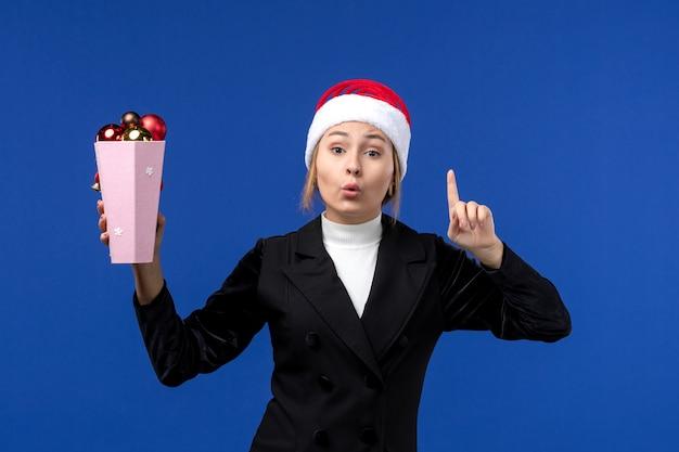 La femmina graziosa dell'albero della tenuta di vista frontale gioca sulla donna blu di festa del nuovo anno della parete blu