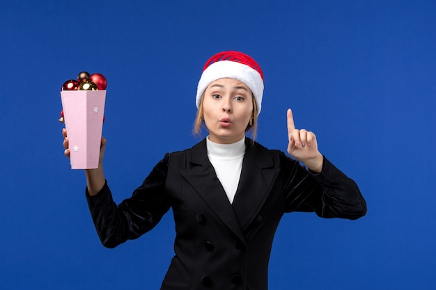 青い壁の新年の青い休日の女性に木のおもちゃを保持している正面図きれいな女性