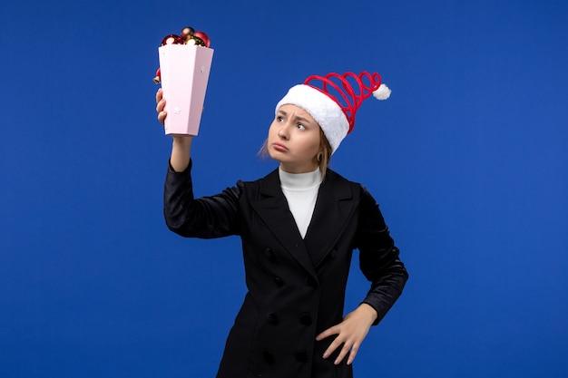 Вид спереди симпатичная женщина, держащая елочные игрушки на синем столе, новогодняя синяя праздничная женщина