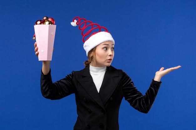 Вид спереди симпатичная женщина, держащая елочные игрушки на синем полу, новогодняя синяя праздничная женщина
