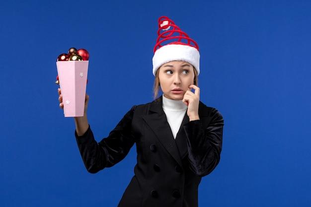 青い壁の新年の青い休日に木のおもちゃを保持している正面図きれいな女性