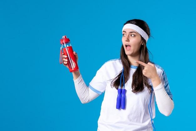 Вид спереди красивая женщина в спортивной одежде со скакалкой на синем