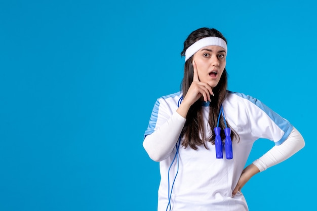 Вид спереди красивая женщина в спортивной одежде со скакалкой