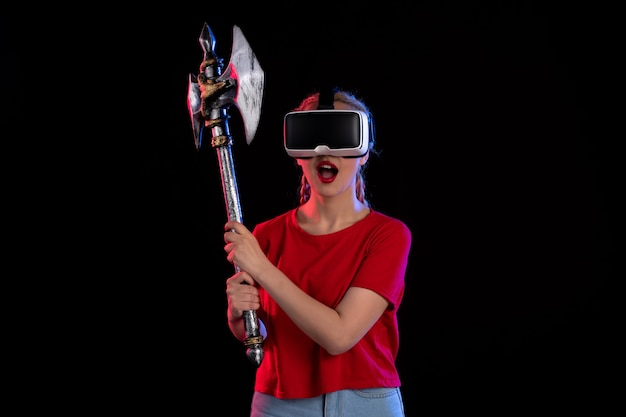 Front view of pretty female playing vr with battle axe dark