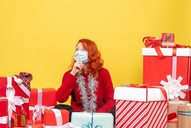 黄色で沈黙を求めてマスクのプレゼントの周りに座っている正面図きれいな女性