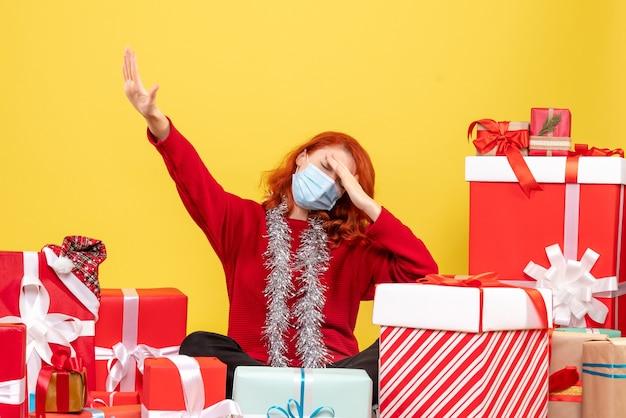 黄色の頭痛を持っているマスクのプレゼントの周りに座っているきれいな女性の正面図