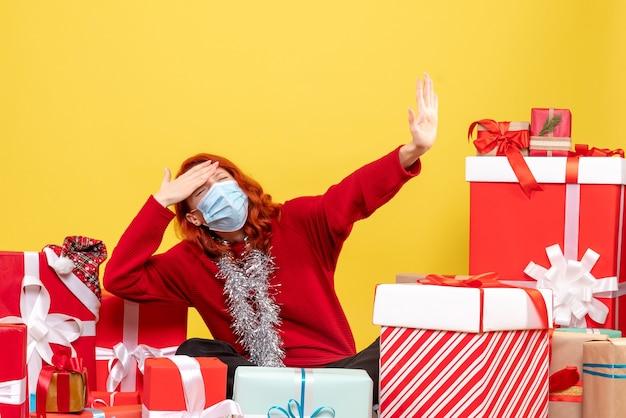 黄色のマスクでプレゼントの周りに座っている正面図きれいな女性