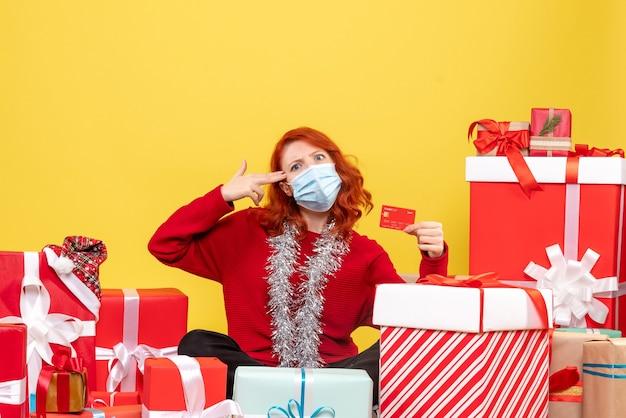 黄色の銀行カードとマスクでプレゼントの周りに座っている正面図きれいな女性