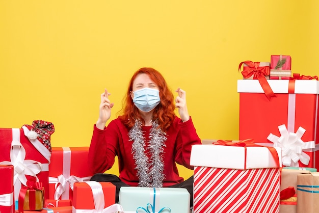 Front view pretty female sitting around presents in mask on yellow desk color new year covid- xmas virus