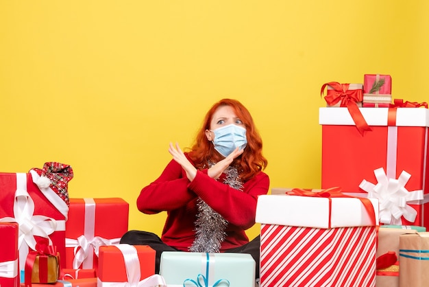 Front view pretty female sitting around presents in mask on yellow desk new year color covid- xmas virus Free Photo