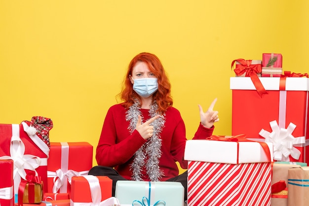 Front view pretty female sitting around presents in mask on yellow floor new year color covid- xmas virus