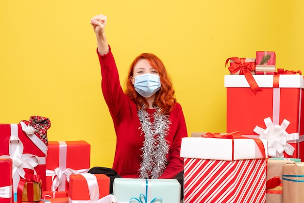 Front view pretty female sitting around presents in mask on yellow Free Photo
