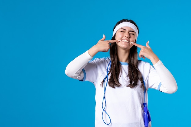 Front view pretty female in sport clothes with skipping rope on blue
