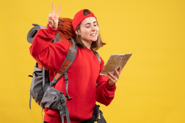 Вид спереди симпатичная путешественница с рюкзаком, держащая карту, жестикулирующую знак победы