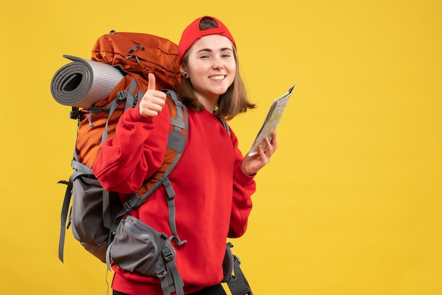 Front view pretty female traveler with backpack holding map giving thumbs up