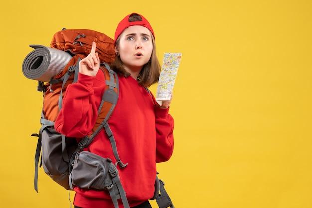 Вид спереди симпатичная путешественница с рюкзаком, держащая карту, указывающую на потолок