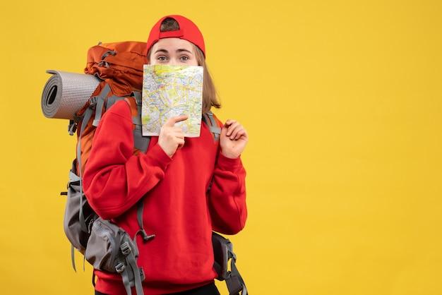Вид спереди симпатичная путешественница с рюкзаком, держащая карту путешествия к лицу