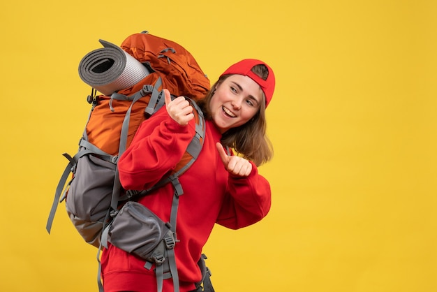 Front view pretty female traveler with red cap pointing at backpack