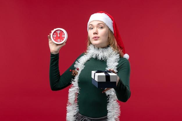 빨간색 배경에 시계와 선물 전면보기 예쁜 여성