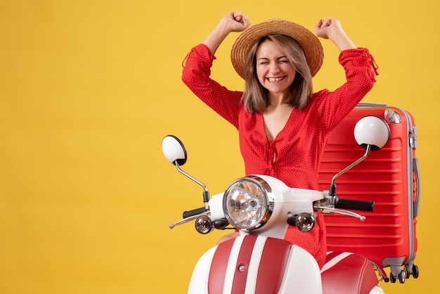 Front view of pretty girl on moped with red suitcase