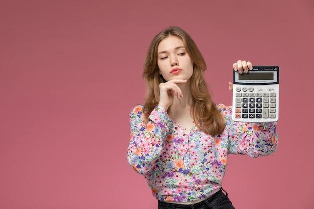 Signora graziosa di vista frontale che esamina la sua calcolatrice