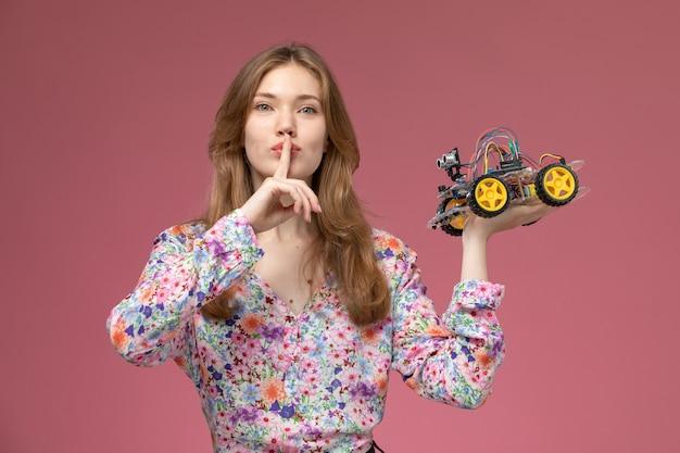 正面図きれいな女性は彼女の車のおもちゃで沈黙のジェスチャーを示しています
