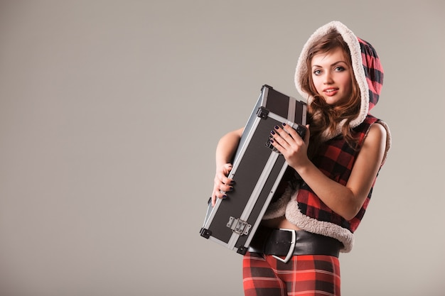 Front view of pretty lady with suitcase looking at camera and smiling. attractive girl wearing checkered pants and hooded vest. isolated on light lilac background. concept of fashion and travel.