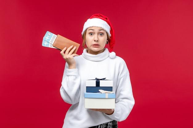 Signora graziosa vista frontale con biglietti e regali su sfondo rosso