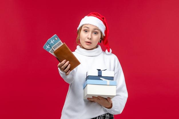 Signora graziosa di vista frontale con biglietti e regali su una scrivania rossa