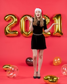Front view pretty woman in black dress balloons on red