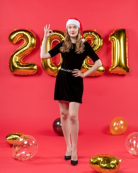 Front view pretty woman in black dress making okey sign balloons on red