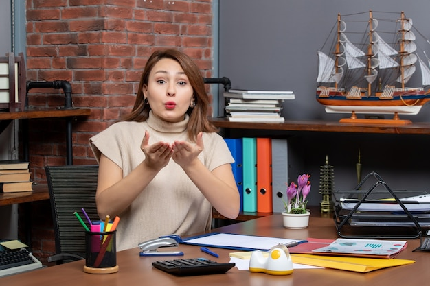 Front view of pretty woman blowing kiss working in office