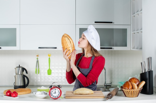 Front view pretty woman in cook hat and apron smelling bread in the kitchen