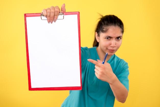 黄色の背景のクリップボードを指している制服を着たきれいな女医師の正面図