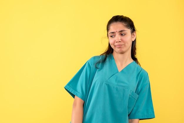 黄色の背景に立っている制服の正面図きれいな女医師