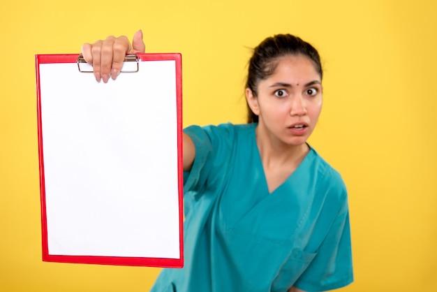 黄色の背景の上にクリップボードが立っている制服を着たきれいな女性医師