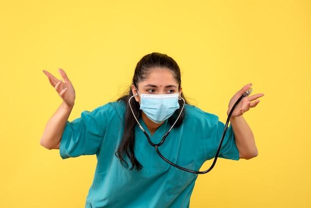 Vista frontale bella donna medico in uniforme tenendo lo stetoscopio in piedi su sfondo giallo