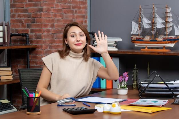 Vista frontale di una bella donna che saluta qualcuno che lavora in ufficio
