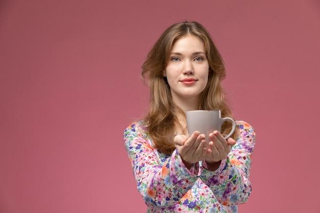 La donna graziosa di vista frontale illustra la tazza con le sue mani