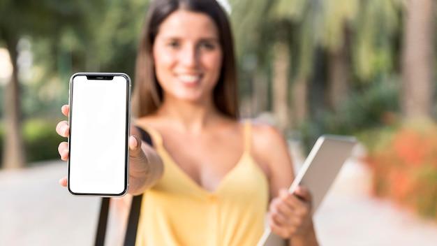 Вид спереди красивая женщина, показывающая свой телефон